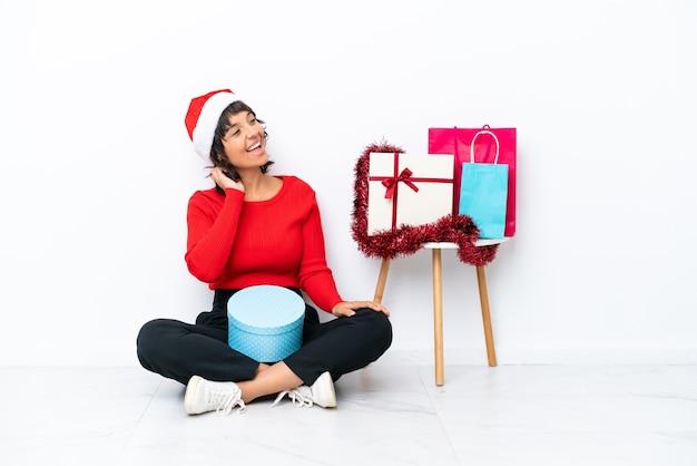 Молодая девушка празднует рождество, сидя на полу, изолированном на белом bakcground, думая об идее