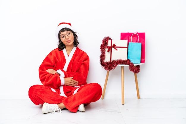 팔짱을 끼고 행복한 흰색 bakcground에 격리된 바닥에 앉아 크리스마스를 축하하는 어린 소녀