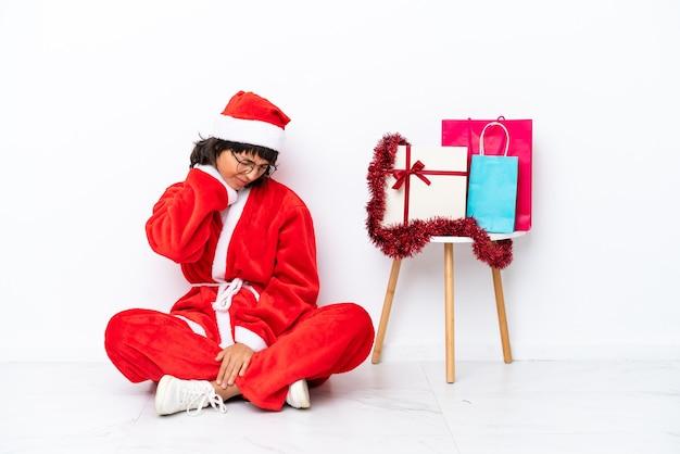 Молодая девушка празднует рождество, сидя на полу, изолированном на белом bakcground с шейной болью