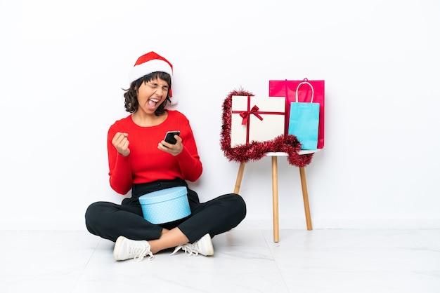 승리 위치에 전화와 흰색 bakcground에 고립 된 바닥에 앉아 크리스마스를 축 하 하는 어린 소녀