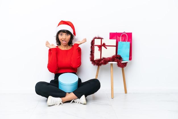 ショックを受けた表情で白いbakcgroundに隔離された床に座ってクリスマスを祝う少女