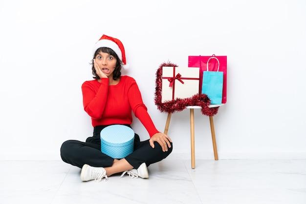 驚きとショックを受けた表情で白いbakcgroundに隔離された床に座ってクリスマスを祝う少女