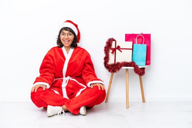 驚きの表情で白いbakcgroundに隔離された床に座ってクリスマスを祝う少女