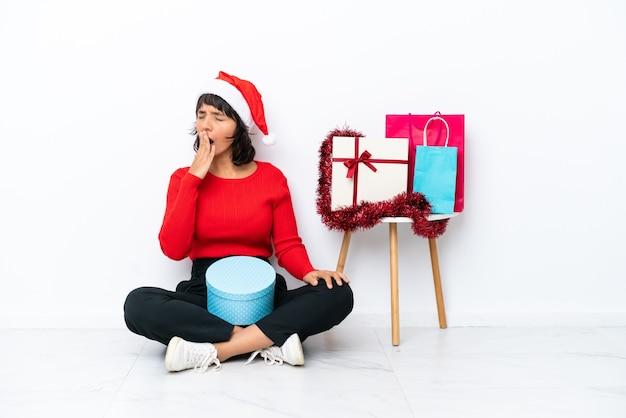 Молодая девушка празднует рождество, сидя на полу, изолированном на белом bakcground, зевая и прикрывая широко открытый рот рукой