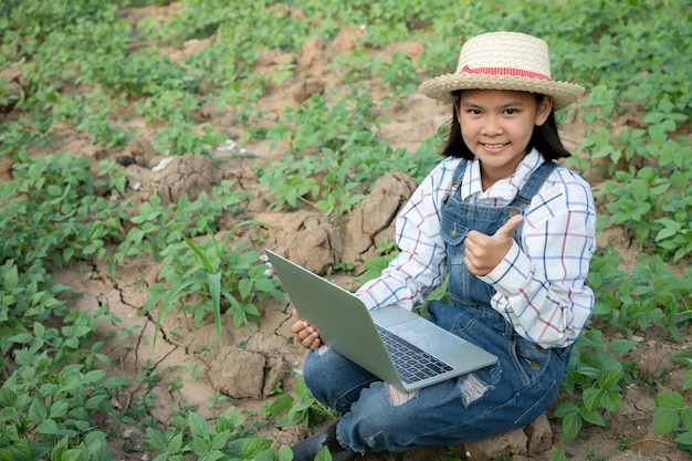 Young girl check and keep the produce of mung bean farm and using a computerized laptop for checking quality. farmer is a profession that requires patience and diligence. being a farmer or gardener.