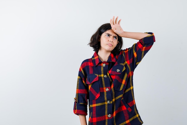 Young girl in checked shirt holding hand on forehead and looking annoyed , front view.
