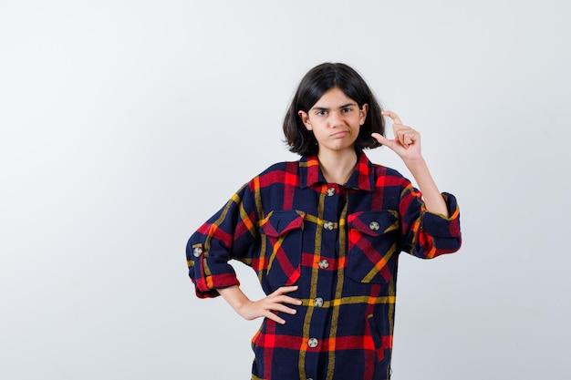 Giovane ragazza in camicia a quadri che tiene la mano sulla vita mentre allunga la mano mentre tiene qualcosa di immaginario e sembra concentrata, vista frontale.