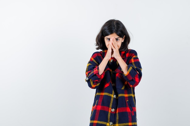 Young girl in checked shirt holding hands clasped and looking excited , front view.