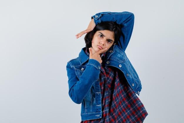 Giovane ragazza in camicia a quadri e giacca di jeans che mette il dito indice sul mento mentre alza la mano sopra la testa e sembra carina