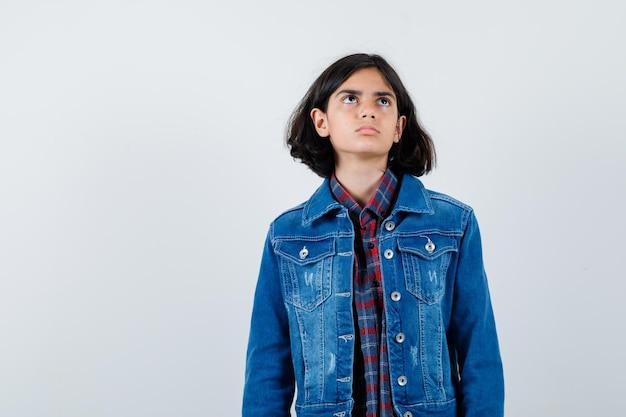 Giovane ragazza in camicia a quadri e giacca di jeans in piedi dritta, guardando sopra e posando alla telecamera e guardando pensierosa, vista frontale.