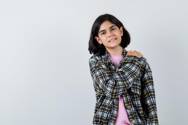 Giovane ragazza in camicia a quadri e t-shirt rosa che mette la mano sulla spalla e sembra carina, vista frontale.