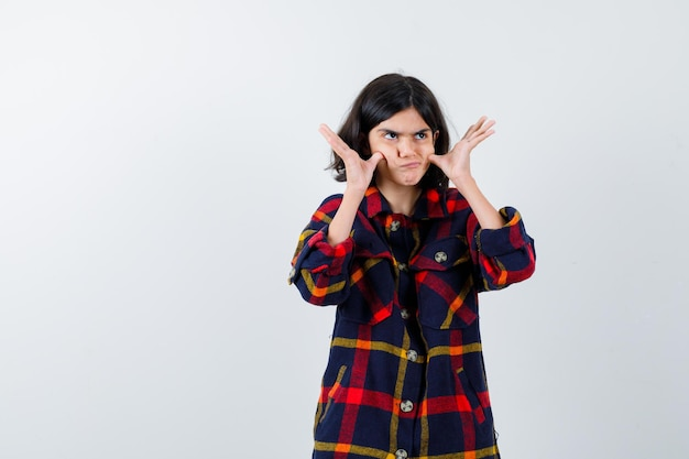 Young girl in checked shirt pulling cheeks with fingers, looking upward and looking pensive , front view.
