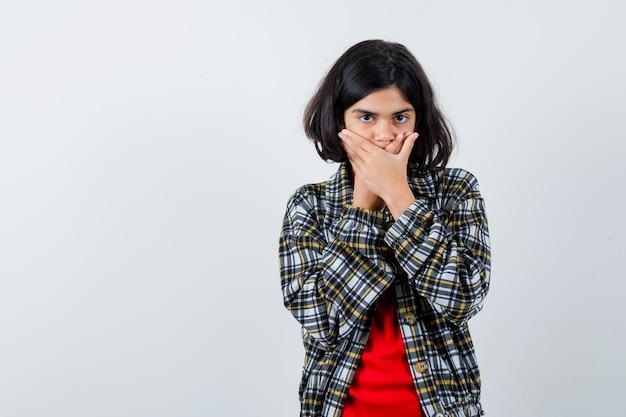 Giovane ragazza in camicia a quadri e maglietta rossa che copre la bocca con le mani e sembra seria, vista frontale.