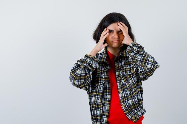 Giovane ragazza in camicia a quadri e t-shirt rossa che si tiene per mano in faccia, sbatte le palpebre e sembra divertita, vista frontale.