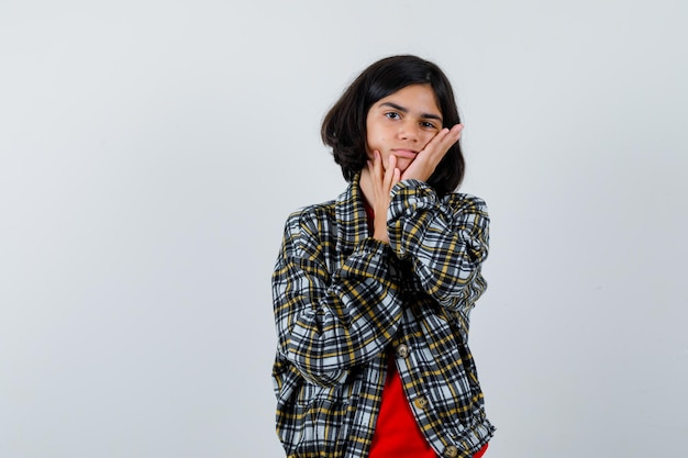 Giovane ragazza in camicia a quadri e t-shirt rossa che si appoggia la guancia sul palmo e sembra carina, vista frontale.