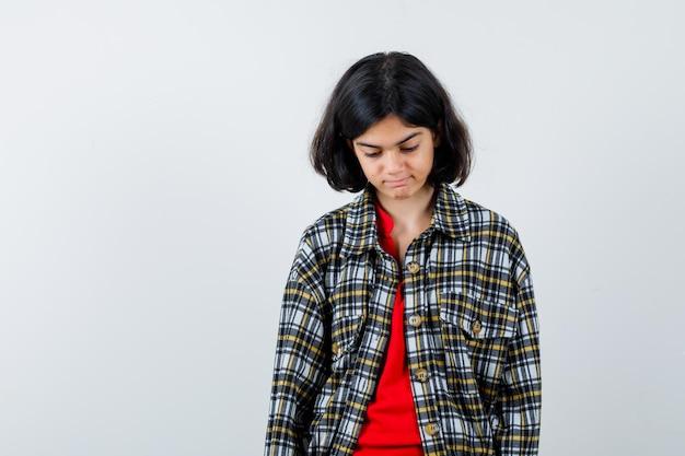 Giovane ragazza in camicia a quadri e t-shirt rossa che guarda in basso e sembra seria, vista frontale.