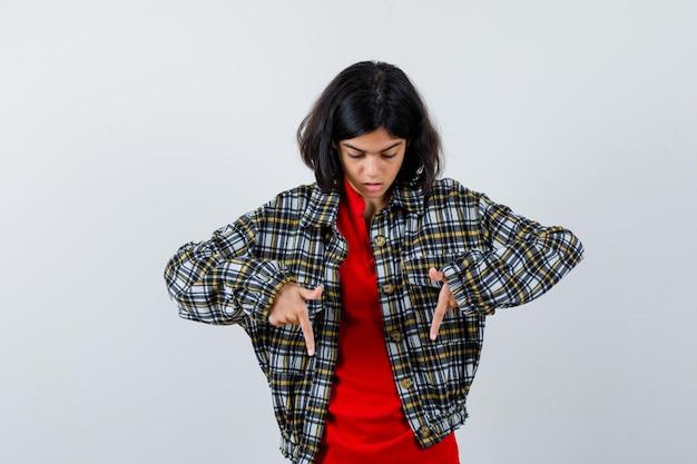 Giovane ragazza in camicia a quadri e t-shirt rossa che punta verso il basso con l'indice e sembra seria, vista frontale.