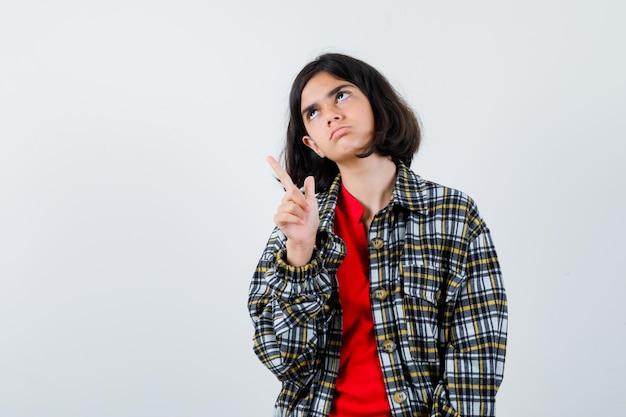Giovane ragazza in camicia a quadri e t-shirt rossa rivolta verso l'alto, guardando sopra e guardando seria, vista frontale.