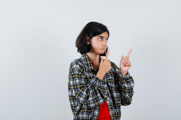 Giovane ragazza in camicia a quadri e t-shirt rossa che punta verso l'alto con l'indice e sembra seria, vista frontale.