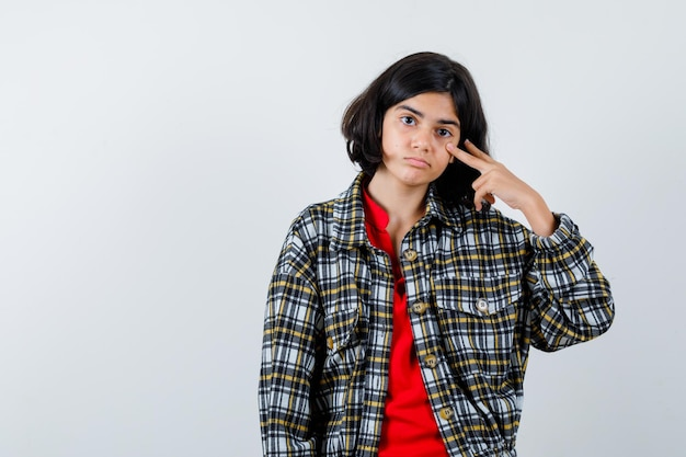 Young girl in checked shirt and red t-shirt showing v sign and looking serious , front view.