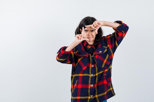 Giovane ragazza in camicia a quadri che mostra il gesto del telaio e sembra carina, vista frontale.