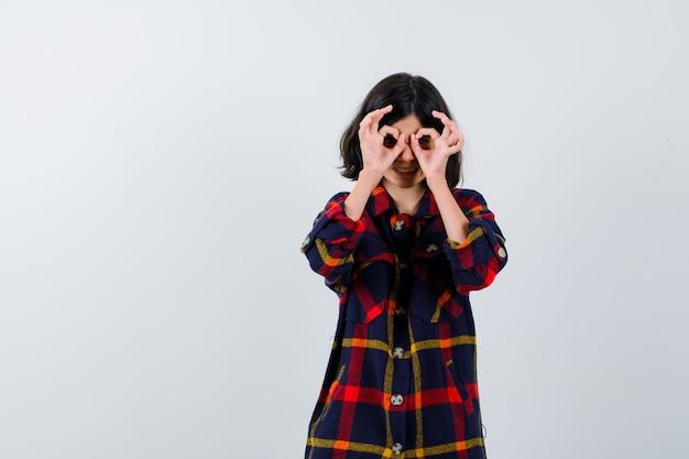 Giovane ragazza in camicia a quadri che mostra segni ok sugli occhi e sembra carina, vista frontale.