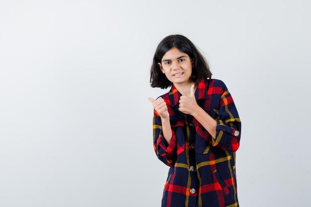 Giovane ragazza in camicia a quadri che mostra i pollici in giù con entrambe le mani e sembra felice, vista frontale.