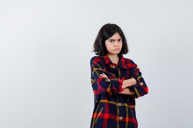 Giovane ragazza in camicia a quadri in piedi con le braccia incrociate e dall'aspetto carino, vista frontale.