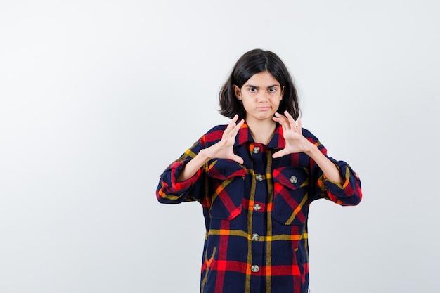 Giovane ragazza in camicia a quadri che allunga le mani mentre tiene qualcosa di immaginario e sembra seria, vista frontale.