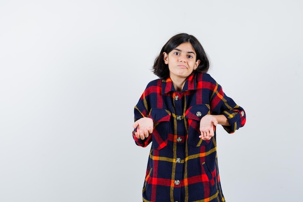 Young girl in checked shirt stretching hands in questioning manner and looking puzzled , front view.