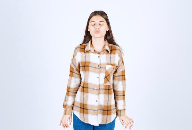 Giovane ragazza in camicia a scacchi che soffia un bacio d'aria.