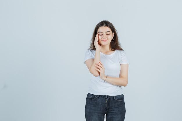 T- 셔츠, 청바지에 사원에 피부를 확인 하 고 기쁘게 찾고 어린 소녀. 전면보기.