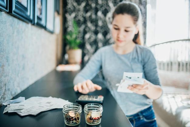 Молодая девушка проверяет счета в своей спальне, перед ней лежат монеты