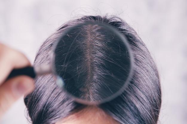 Молодая девушка проверяет свои волосы