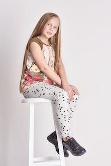 Young girl child with long hair sitting on a chair. smile joy emotions on her face