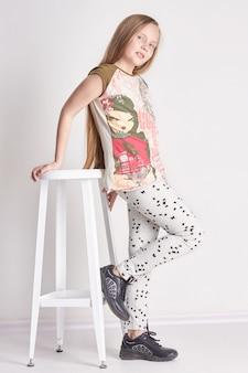 Маленькая девочка с длинными волосами, сидя на стуле