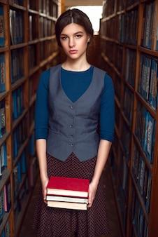 若い女の子は読書のための本を選択します。