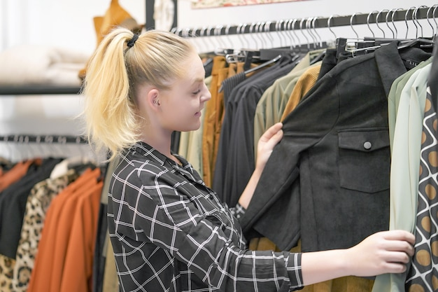 Young girl chooses things in a clothing store