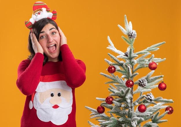 Giovane ragazza in maglione di natale che indossa la fascia divertente pazzo felice che copre le orecchie che grida in piedi accanto a un albero di natale oltre la parete arancione