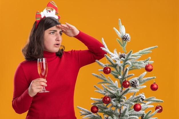 Giovane ragazza in maglione di natale indossando la fascia divertente tenendo un bicchiere di champagne guardando lontano con la mano sopra la testa in piedi accanto a un albero di natale oltre la parete arancione