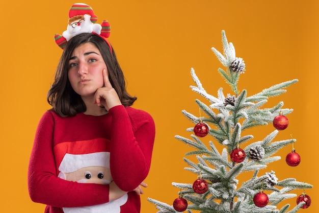 Giovane ragazza con un maglione natalizio che indossa una fascia divertente che guarda da parte perplessa in piedi accanto a un albero di natale su sfondo arancione