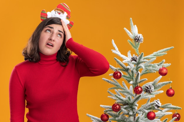 Young girl in christmas sweater wearing funny headband rolling eyes up tired and bored standing next to a christmas tree over orange wall