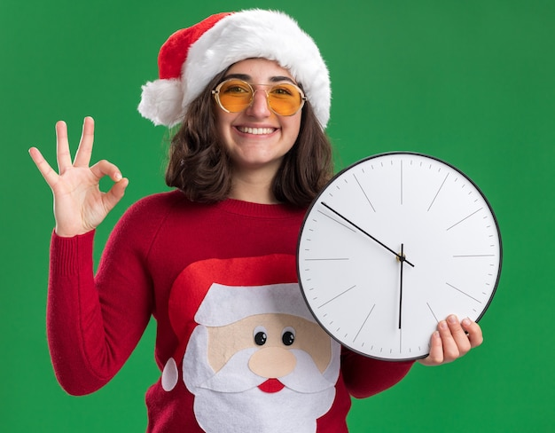 Young girl in christmas sweater wearing santa hat and glasses holding wall clock looking at camera with smile on face showing ok sign standing over green background