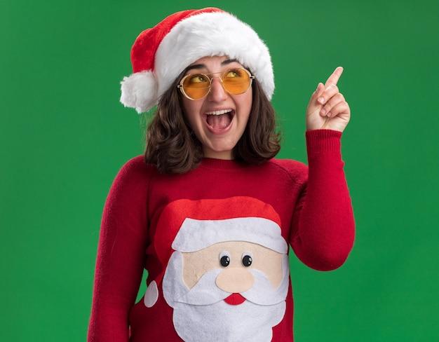 Giovane ragazza in maglione di natale che indossa cappello santa e occhiali cercando felice e allegro che punta con il dito indice in alto in piedi sopra la parete verde