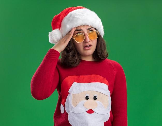 Giovane ragazza in maglione di natale che indossa il cappello della santa e occhiali roteando gli occhi stanchi e annoiati in piedi sopra la parete verde
