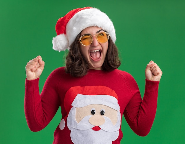 Young girl in christmas sweater wearing santa hat and glasses shouting excited and crazy happy clenching fists standing over green wall