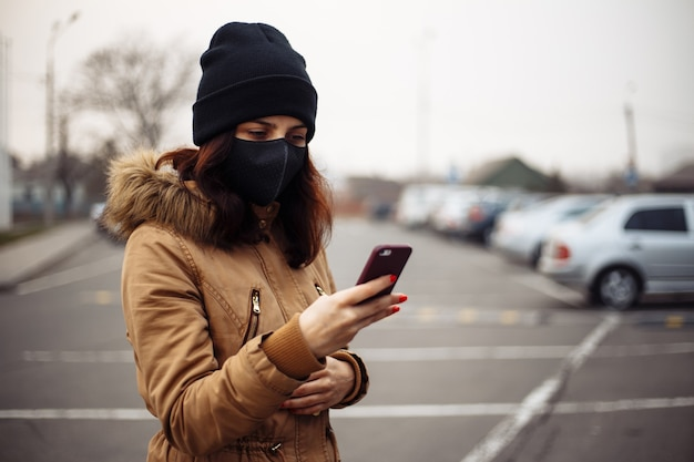 Young girl in city street wearing black sterile medical face mask. woman using the phone to search for news about ncov 2019. quarantine covid-19 pandemic coronavirus epidemic and health care concept.