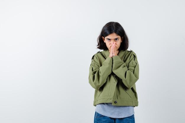 회색 스웨터, 카키색 재킷, 진 바지를 입은 어린 소녀가 기도 자세로 손을 꼭 잡고 진지한 표정을 짓고 있습니다. 전면보기.