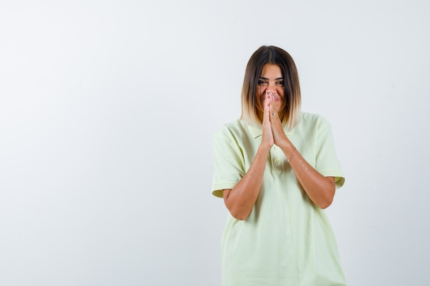 若い女の子は、tシャツの祈りの位置で手を握りしめ、陽気に見えます。正面図。