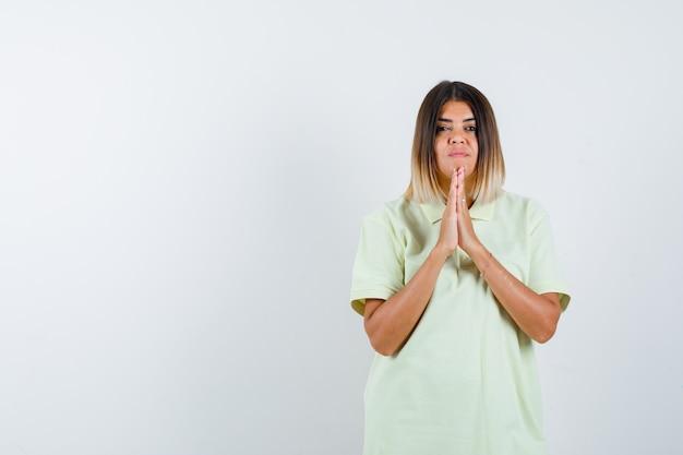 Молодая девушка, сложив руки в молитвенной позиции в футболке и серьезная, вид спереди.